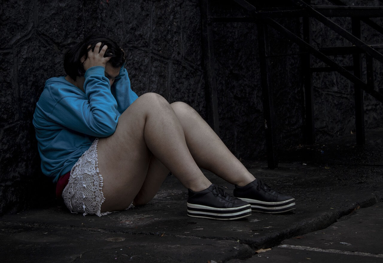 Image of a sad girl sitting on the floor